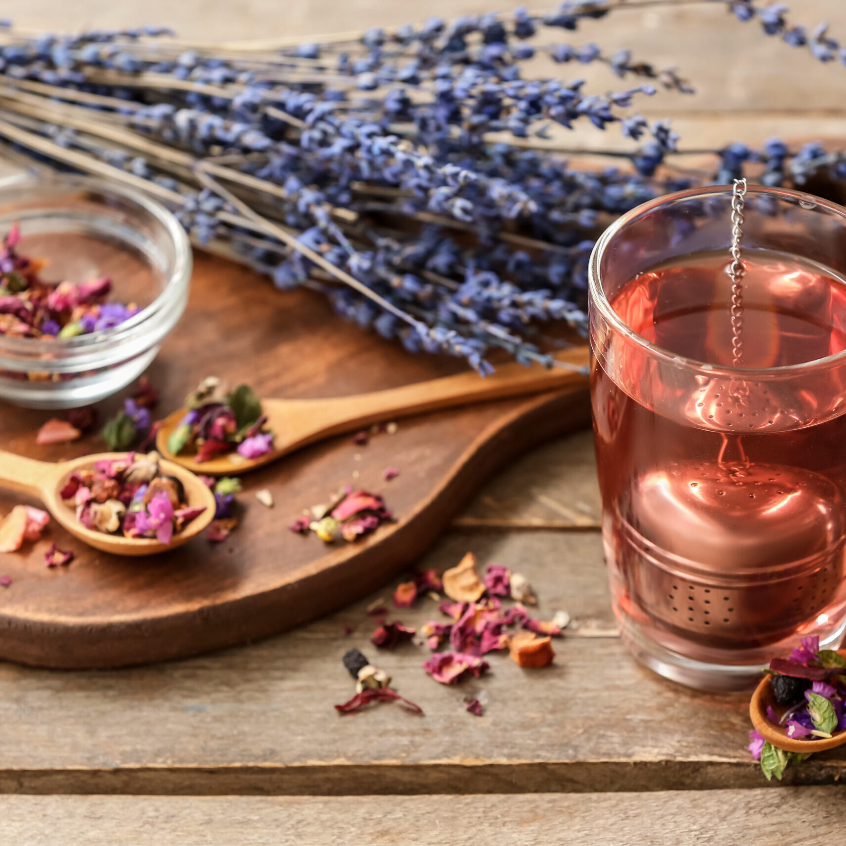 Cup with floral tea and dry flowers in spoons on wooden background