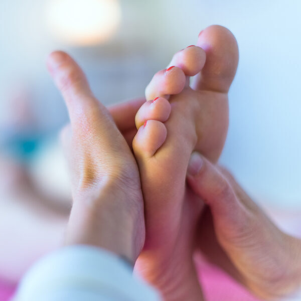Close up of therapist's hands massaging female foot
